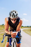 Triathlon cyclist navigating on smartphone — Stock Photo
