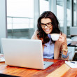 Lady holding coffee and using laptop — Stock Photo #39154505