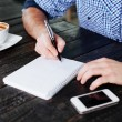 Man writing in notepad — Stock Photo