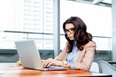Pretty woman typing on her laptop — Stock Photo