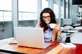 Lady holding coffee and using laptop — Stock Photo