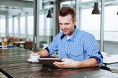 Professional at canteen table with tablet — Stock Photo