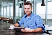 Man enjoying coffee and using tablet — Stock Photo