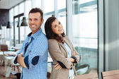 Smiling couple standing back to back — Stock Photo