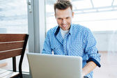 Positive young man using his laptop — Stockfoto