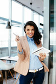 Female assisstant with ballpen and notepad — Stock Photo