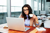 Woman holding cup and browsing net — Stock Photo