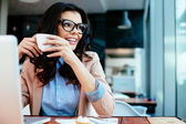 Lady drinking coffe and looking through window — Stock Photo
