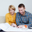 Happy couple and looking at blueprint — Stock Photo