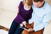 Hugging couple using a digital tablet — Stock Photo