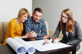 Couple discussing blueprints with architect — Stock Photo