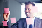 Manager writing an idea on a sticky note — Stock Photo