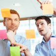 Businessmen discussing ideas on sticky notes — Stock Photo #47778341