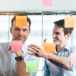 Businessmen discussing ideas on sticky notes — Stock Photo #47778349