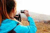 Female backpacker taking a photo — Stock Photo