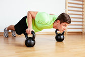 Man doing push-ups on kettlebells — Photo