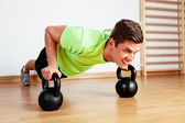 Sportsman sculpting body with kettlebells — Stock Photo