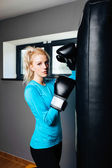 Woman relaxing near boxing bag — Photo