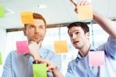 Businessmen discussing ideas on sticky notes — Stockfoto