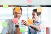 Businessmen discussing ideas on sticky notes — Stock Photo