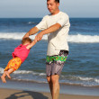 Stock Photo: Dad with a child playing on the shore of the sea