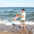 Dad with a child playing on the shore of the sea — Stock Photo