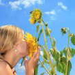 Girl smelling a sunflower on sky background - Stockfoto