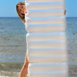 Woman with a mattress on the sea shore - Stock Photo