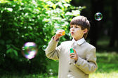 Boy in school uniform with soap bubbles — Stok fotoğraf