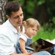 Stock Photo: Dad and daughter reading the Bible
