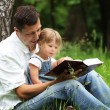 Dad and daughter reading the Bible — Stok fotoğraf