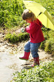 Beautiful little girl outdoors in rubber boots — Stock Photo