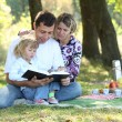 Young family with a child reading the Bible — Stock Photo