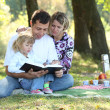 Young family with a child reading the Bible — Stock Photo #13412441