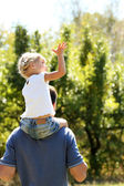 Beautiful little girl playing with her father in nature — Stock Photo