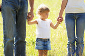 Beautiful little girl holding the hand of her father and mother on the nature — Stock Photo