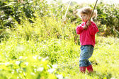 Beautiful little girl outdoors near a lake in rubber boots — Stock Photo