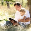 Young father with his daughter reads the Bible — Stock Photo #13831722