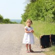 Beautiful little girl by the road with a suitcase — Stock Photo
