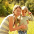 Beautiful little girl with her mother outdoors — Stock Photo #13831827