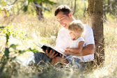 Young father with his daughter reads the Bible — Stock Photo