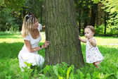 Beautiful little girl with mother near tree on nature — Stock Photo