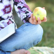 Young woman eating an apple and reading a book the Bible — Stock Photo