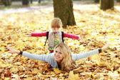 Jovem mãe e sua filha sobre a natureza — Fotografia Stock