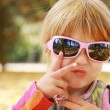 Beautiful little girl in sunglasses in the autumn forest — Stock Photo