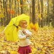 Beautiful little girl in the autumn forest with umbrella — Stock Photo