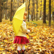 Beautiful little girl in the autumn forest with umbrella — Stock Photo #18005765