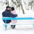 Couple in winter park on a bench — Stock Photo