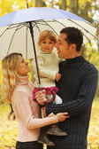 Family with beautiful little girl with umbrella in the autumn forest — Stock Photo