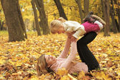Beautiful little girl play with her mother in the autumn forest — Stock Photo